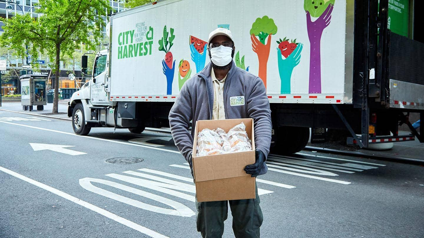 A man holding a box of food on a street in New York.