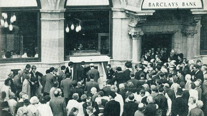 Crowd watches the unveiling of the world's first ATM
