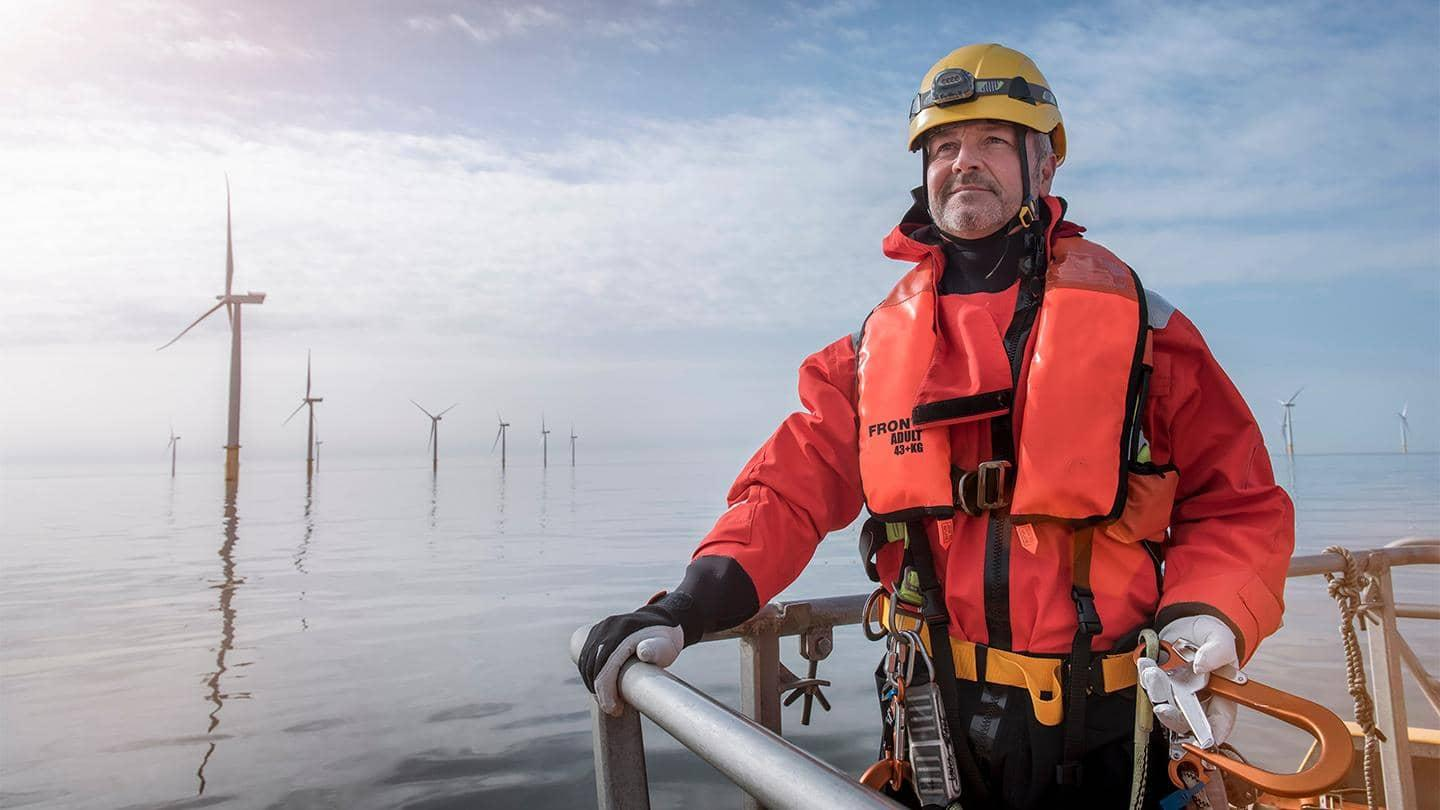 A man wearing a life jacket and helmet, standing by water with wind turbines.