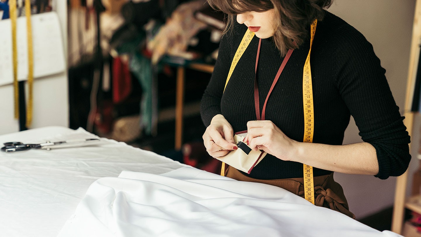 A woman adds pins to material.