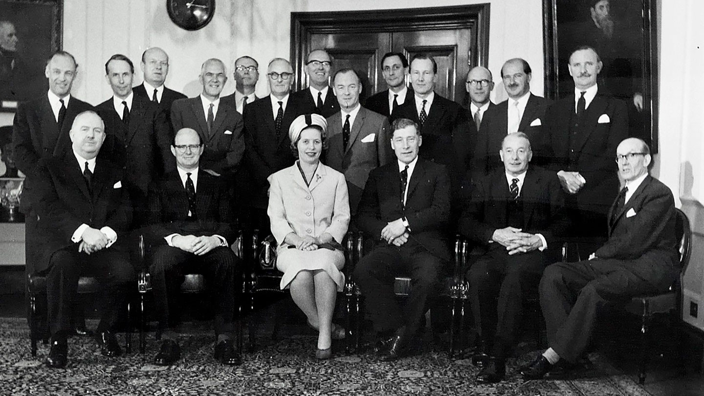 Harding is the only woman among a large group of businessmen.