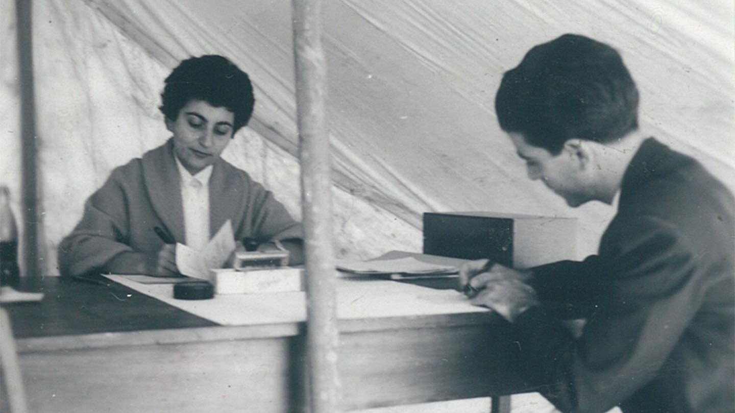 Araxie Yaghlian sits at her desk inside a tent, writing.