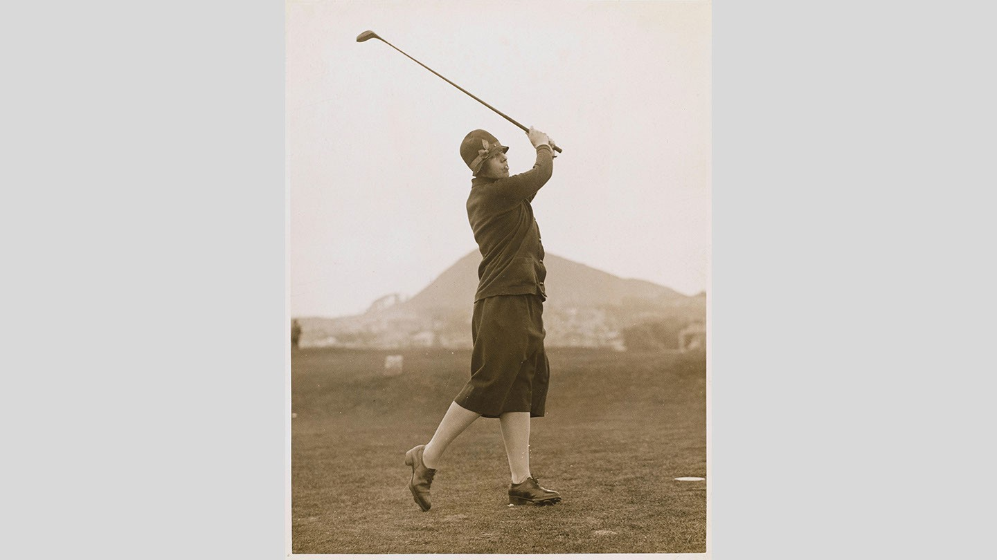 Miriam Pease swings a club on a golf course.